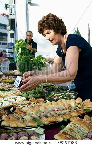 Montenegro, Herceg Novi - 18/06/2016: A woman prepare a table with treats for the guests of the festival. 12 gastronomic festvial