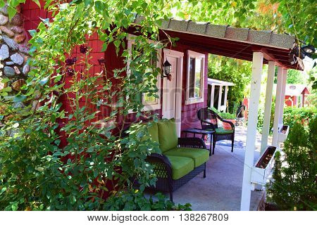 Rustic cottage with outdoor furniture on the front porch surrounded by a lush green garden