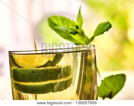 Alcohol drink. On wooden boards is glass with alcohol green transparent drink. A drink number hundred fifty one cocktail mohito with slice lime and mint . Country life. Outdoor. Light background.