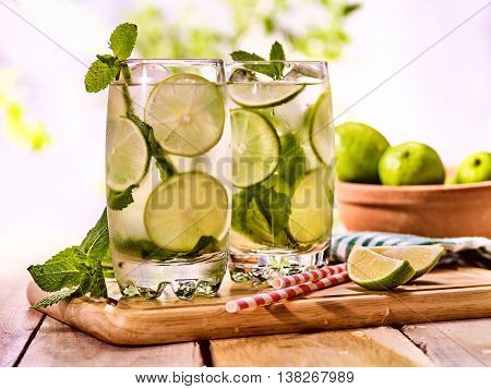 Alcohol drink. On wooden boards two glasses with alcohol drink and ice cubes.Drink number hundred forty cocktail lime mohito with straw and mint leaf. Country life. Outdoor. Light background.