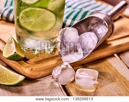 Ice scoop and alcohol drink. On wooden boards is glass with alcohol drink and ice cubes. Drink number hundred forty two of part cocktail mohito and scoop ice . Country life. Outdoor. Light background.