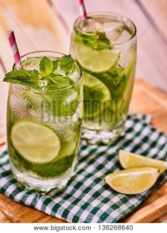 Alcohol drink. On wooden boards two glasses with alcohol drink and ice cubes. Drink number hundred forty five cocktail mohito and mint leaf on checkered cloth. Country life. Light background.
