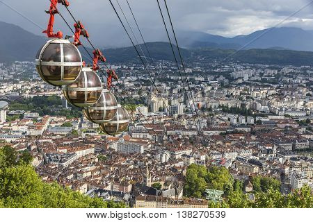 GRENOBLE, FRANCE - JUNE 19, 2016: Picturesque aerial view of Grenoble city France. Grenoble-Bastille cable car on the foreground (French: Telepherique de Grenoble Bastille)