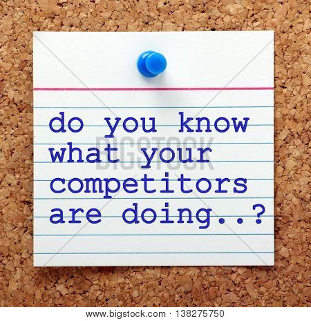 The question Do You Know What Your Competitors Are Doing in blue typescript on a paper note pinned to a cork notice board