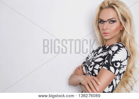 beautiful lush blond curly hair sexy model with green eyes in glasses in the whit black elegant short sexy dress and white pants on a white background