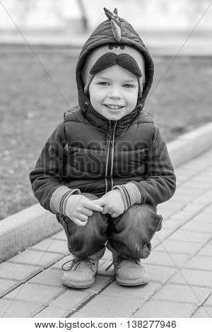 Happy Toddler boy sitting on his haunches outdoors (black and white)