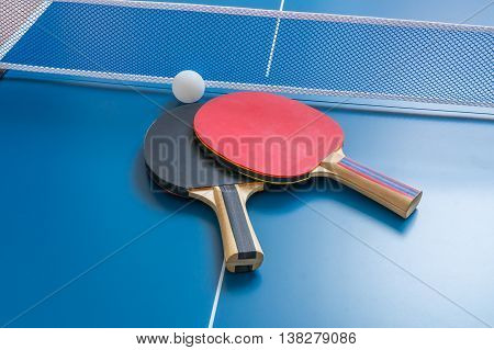 Ping Pong Rackets With Net On Blue Table.