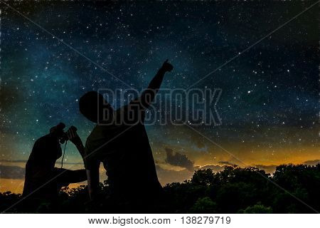 Man and child are observing night sky.