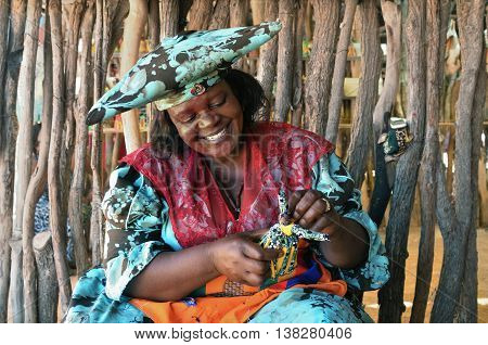 KAOKOLAND NAMIBIA - FEB 1 2016: Smiling Herero Woman in traditional clothes makes a doll. The Herero belonging to the Bantu group with about 240000 members alive today.