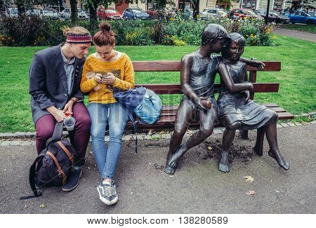 Pilsen Czech Republic - October 3 2015. Young couple sits on a bench with sculptures created by Lea Vivot in Pilsen (Plzen) city