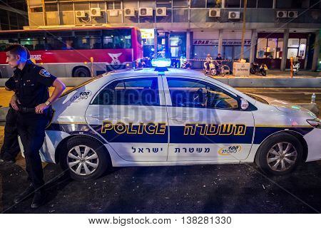 Tel Aviv Israel - October 18 2015. Police officer stands next to police car on the street in Tel Aviv