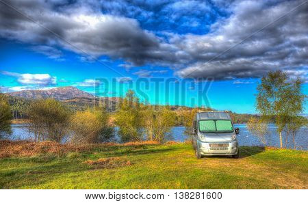 Campervan wildcamping in Scotland by Scottish Loch Garry UK with mountains in summer colourful HDR