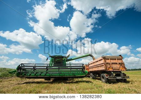 Combine harvester transferring freshly harvested wheat to tractor-trailer for transport