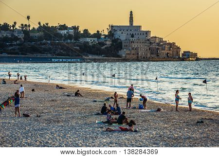 Tel Aviv Israel - October 21 2015. People rests on the beach. View with buildings of Jaffa also called Japho or Joppa former port city now part of Tel Aviv