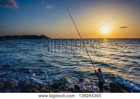 Tel Aviv Israel - October 21 2015. Angler fishes from the shore of the Mediterranean Sea in Tel Aviv