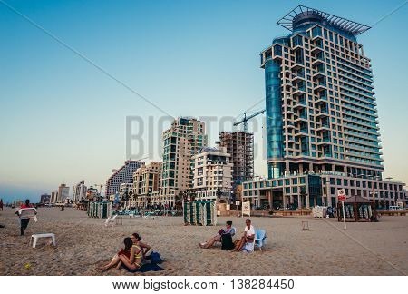 Tel Aviv Israel - October 21 2015. People sits on the beach in Tel Aviv. View with Sea One Tower building on the right side