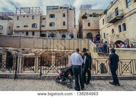 Jerusalem Israel - October 22 2015. Group of Jews stands on the street of Jewish Quarter next to ancient street called Cardo