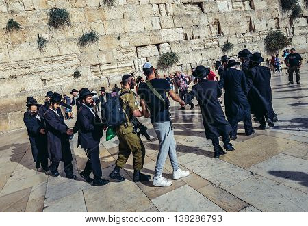 Jerusalem Israel - October 22 2015. Group of Orthodox Jews dances with Israeli soldiers next to ancient limestone wall known as Wailing Wall in the Old City of Jerusalem