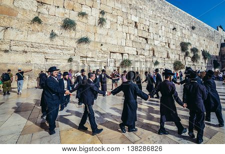 Jerusalem Israel - October 22 2015. Group of Orthodox Jews dances next to ancient limestone wall known as Wailing Wall in the Old City of Jerusalem