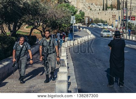 Jerusalem Israel - October 22 2015. Officers of Israeli Border Police called Magav passes next to Orthodox Jew in Jerusalem city