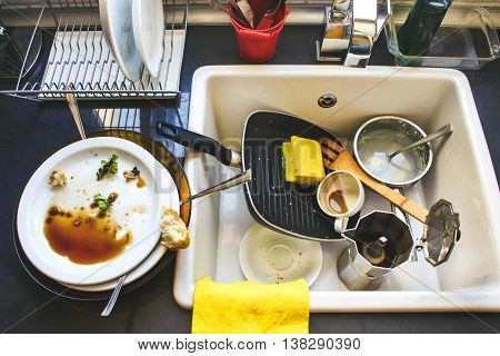 A lot of dirty dishes in the white sink in the kitchen