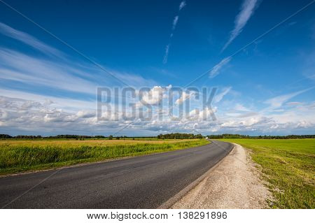 Green field with Country road. Summer landscape with clouds.