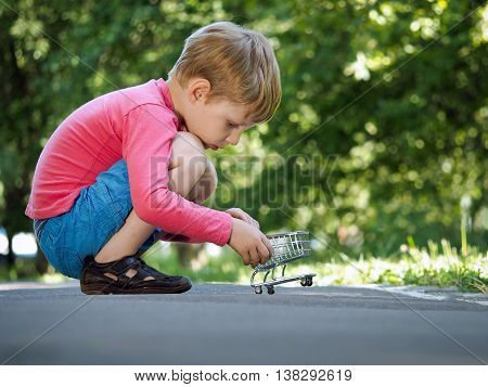 Boy on a path in a park with a small supermarket trolley. The concept of children's goods online shopping