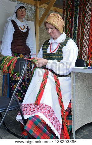 VILNIUS, LITHUANIA - MAY 24 : Unidentified people performs traditional craft of weaving in the street during a International Folklore Festival on May 24 2013 in Vilnius, Lithuania.