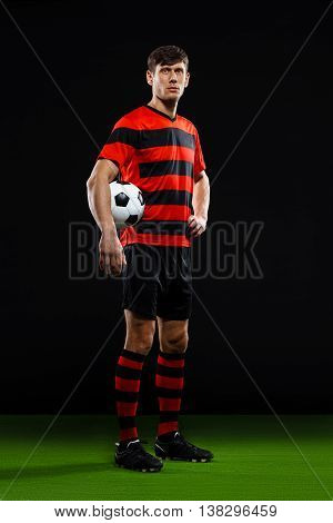 Soccer player in black and red uniform with ball in hand standing on grass over black background, looking at camra