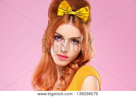 Fashion portrait woman with Pinup hairstyle, Trendy fashion Makeup. Beauty sexy redhead Model, Glamor Stylish Fashion doll, eyelashes. Playful model Pinup fashion girl on pink.Unusual creative emotion