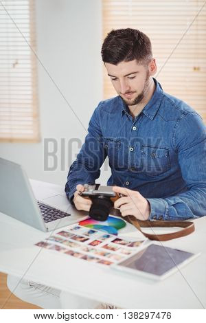 Photographer checking photos in camera at desk in office