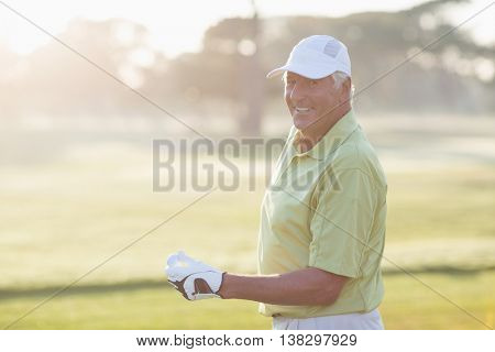 Portrait of smiling mature golfer standing on field