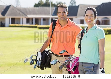 Portrait of couple carrying golf bags while standing on field
