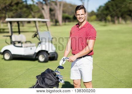 Portrait of smiling man holding golf club while standing on field