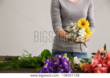 Girl in gray blouse and jeans make bouquet of herberas and alstroemerias over gray background, flowers on wood table.