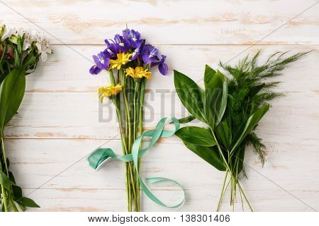 Bright colorful irises, herberas and alstroemerias in green ribbon on wood table. From above.