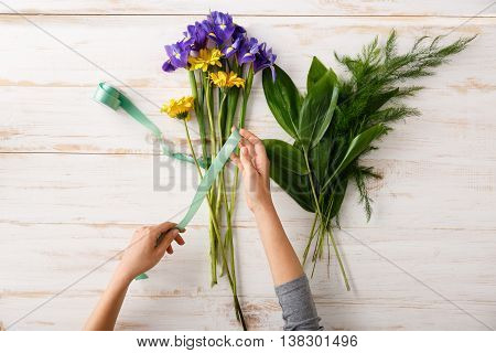 Bright colorful irises and herberas with green ribbon in hands on wood table. From above.