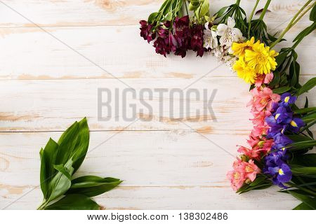Colorful bright alstroemerias, irises and herberas on wood table. From above.