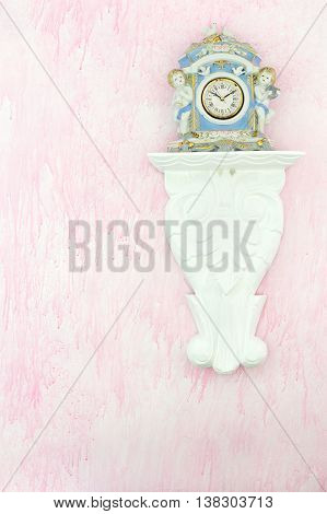 Vintage porcelain clock with cherubs and doves on a carved white shelf against a pink background. Feminine shabby chic style. Copy space. poster