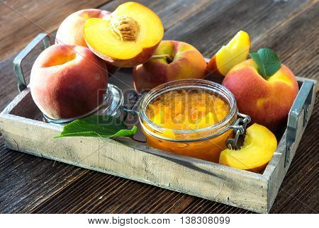 Peach Jam And Fresh Peaches On Wooden Background