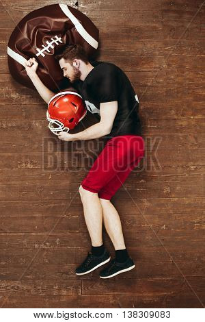 Top view photo of handsome young american football player on wooden floor. Man with uniform and equipment