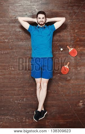 Top view photo of handsome young sportsman on wooden floor. Man with ping pong rackets