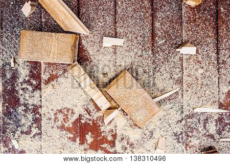 Close up of cutters of wood lying among sawdust, wooden bricks, wood chips. Studio shot, workshop floor background.