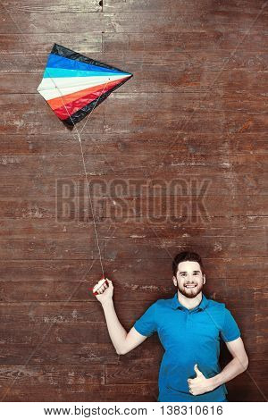Top view photo of handsome young man on wooden floor. Man with colorful kite