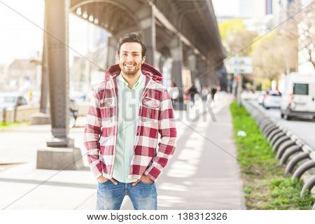 Portrait of an handsome young man in Hamburg. He is middle eastern on his early twenties. He is looking at camera and smiling. Real people portrait with candid expression