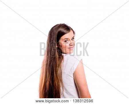 Teenage girl in black striped longsleeved t-shirt, young beautiful woman, studio shot on white background, isolated, rear view