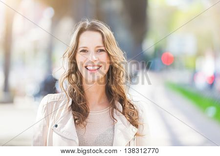 Portrait of a beautiful young woman in Hamburg. She is caucasian on her early twenties brunette with long hair. Looking at camera and smiling. Smart casual clothes blurred urban background
