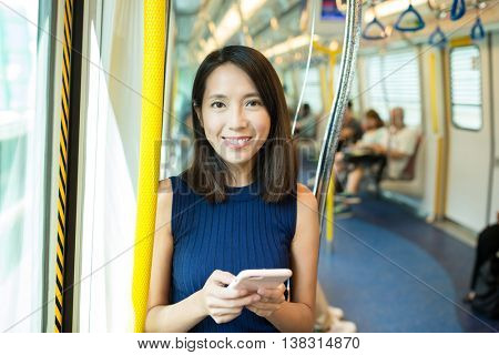 Woman using mobile phone in metro compartment