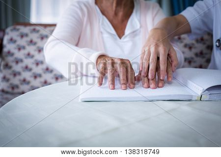 Mid section of female doctor helping a blind patient in reading the braille book