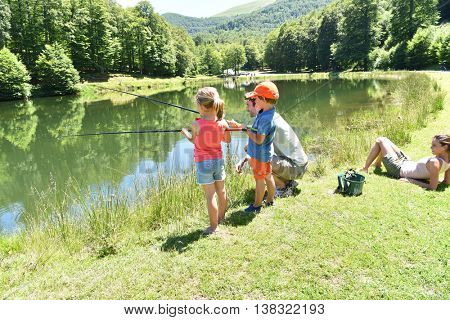 Daddy with kids fishing together by mountain lake